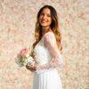 Braut vor Blumenwand Champagner