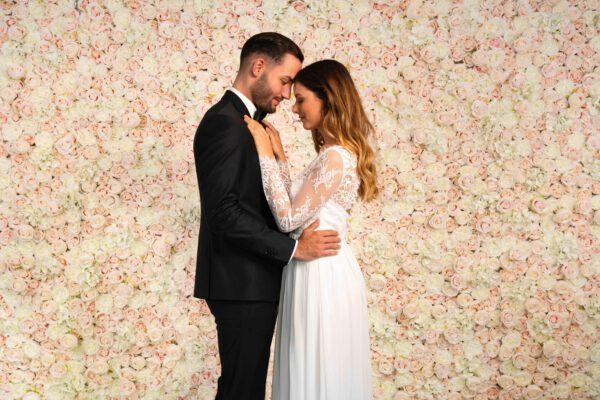 Brautpaar verliebt vor Blumenwand Champagner