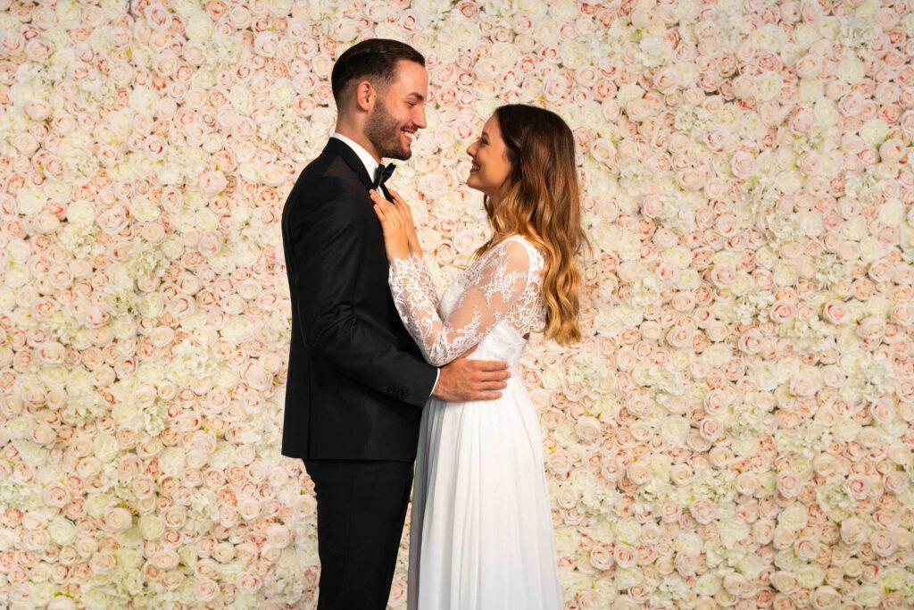 Brautpaar glücklich vor Blumenwand Champagner