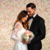 Brautpaar lächelnd vor Blumenwand Champagner
