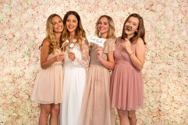 Mädels vor Blumenwand Champagner