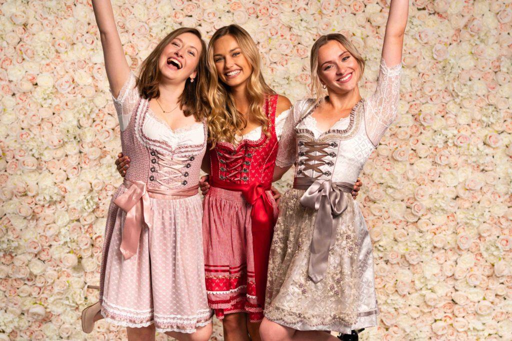 Mädels in Dirndl glücklich vor Blumenwand Champagner