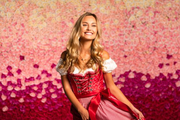 Frau in Dirndl vor Blumenwand Pink Ombré